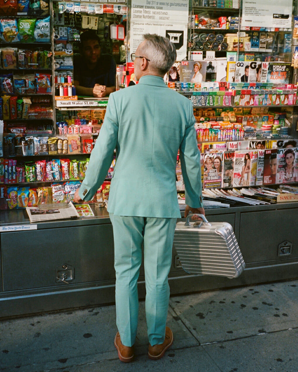 Man in a teal suit stops by magazine stand in a street style shot.